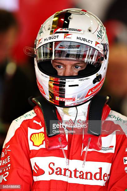 Sebastian Vettel of Germany and Ferrari wears his helmet in the garage during practice for the Formula One Grand Prix of Great Britain at Silverstone...