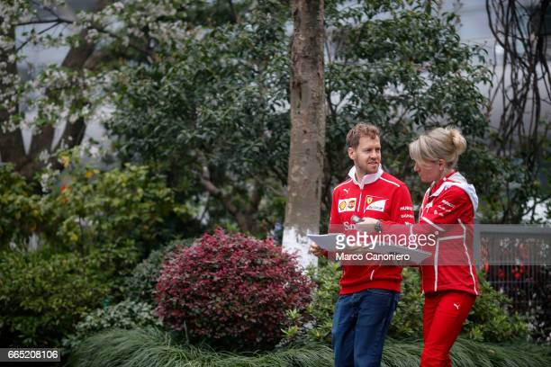 Sebastian Vettel of Germany and Ferrari with Britta Roeske Ferrari Press Officer in the Paddock during previews to the Formula One Grand Prix of China