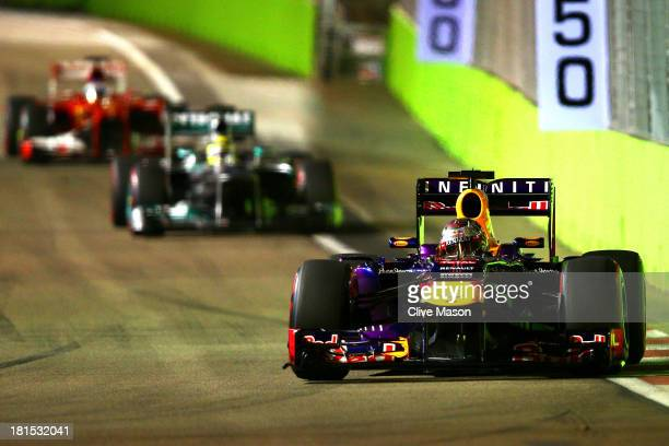 Sebastian Vettel of Germany and Infiniti Red Bull leads Nico Rosberg of Germany and Mercedes GP and Fernando Alonso of Spain and Ferrari during the...