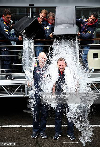 Sebastian Vettel of Germany and Infiniti Red Bull Racing and Daniel Ricciardo of Australia and Infiniti Red Bull Racing pour buckets of ice water...