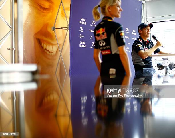 Sebastian Vettel of Germany and Infiniti Red Bull Racing and his press officer Britta Roeske are seen attend a media session during previews to the...