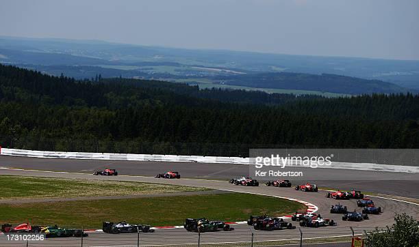 Sebastian Vettel of Germany and Infiniti Red Bull Racing and Mark Webber of Australia and Infiniti Red Bull Racing lead the field at the start of the...