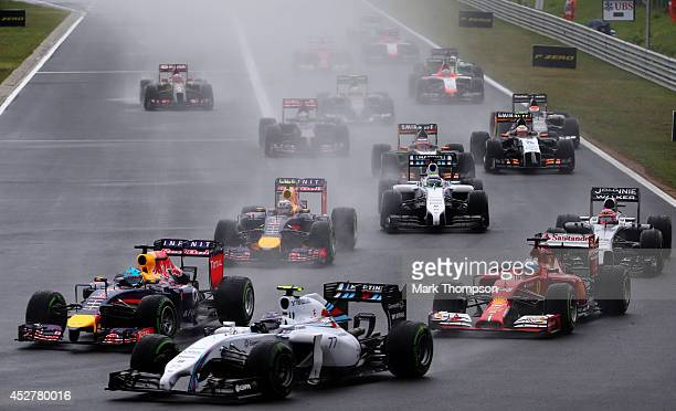 Sebastian Vettel of Germany and Infiniti Red Bull Racing and Valtteri Bottas of Finland and Williams enter turn one during the Hungarian Formula One...