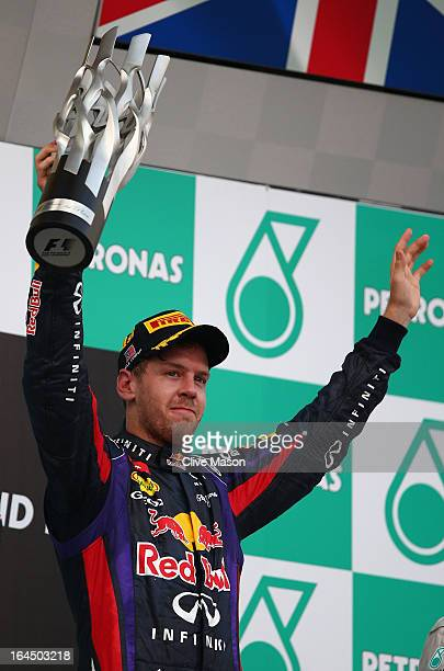 Sebastian Vettel of Germany and Infiniti Red Bull Racing celebrates on the podium after winning the Malaysian Formula One Grand Prix at the Sepang...