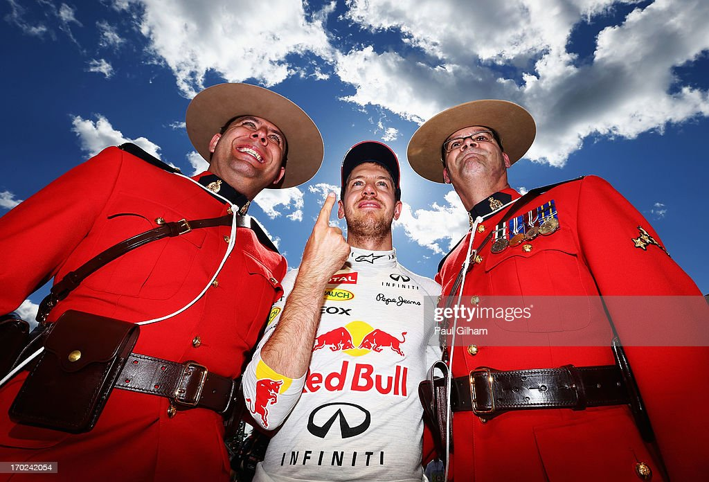Sebastian Vettel of Germany and Infiniti Red Bull Racing celebrates with two Canadian Mounties after winning the Canadian Formula One Grand Prix at the Circuit Gilles Villeneuve on June 9, 2013 in Montreal, Canada.
