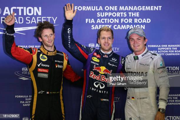 Sebastian Vettel of Germany and Infiniti Red Bull racing celebrates his pole position with Romain Grosjean of France and Lotus and Nico Rosberg of...