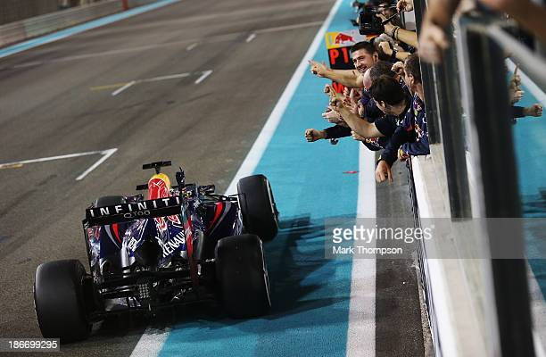 Sebastian Vettel of Germany and Infiniti Red Bull Racing celebrates in front of team mates as he crosses the finishing line to win the Abu Dhabi...
