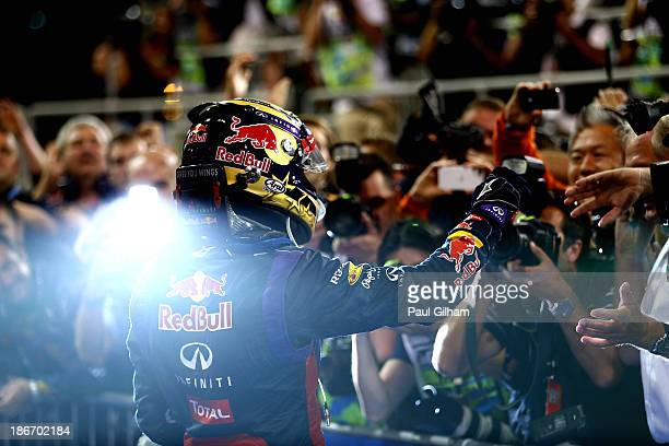 Sebastian Vettel of Germany and Infiniti Red Bull Racing celebrates in parc ferme after winning the Abu Dhabi Formula One Grand Prix at the Yas...