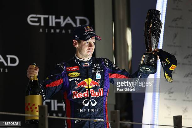 Sebastian Vettel of Germany and Infiniti Red Bull Racing celebrates on the podium after winning the Abu Dhabi Formula One Grand Prix at the Yas...