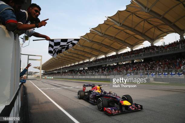 Sebastian Vettel of Germany and Infiniti Red Bull Racing crosses the finish line to win the Malaysian Formula One Grand Prix at the Sepang Circuit on...