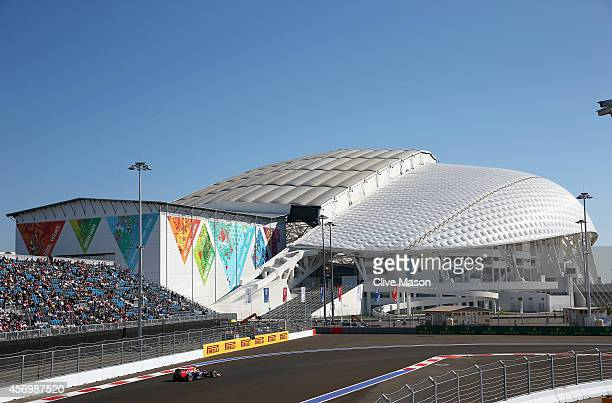 Sebastian Vettel of Germany and Infiniti Red Bull Racing drives past the Fisht Olympic Stadium during practice ahead of the Russian Formula One Grand...