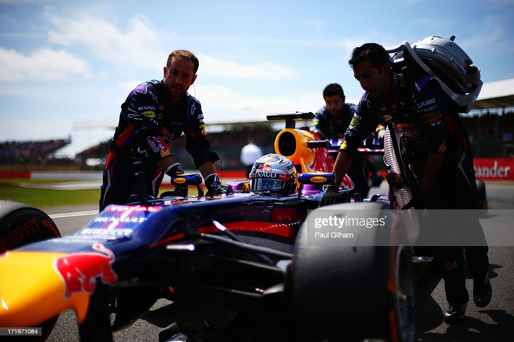 Sebastian Vettel of Germany and Infiniti Red Bull Racing is pushed onto the grid before the British Formula One Grand Prix at Silverstone Circuit on June 30, 2013 in Northampton, England.