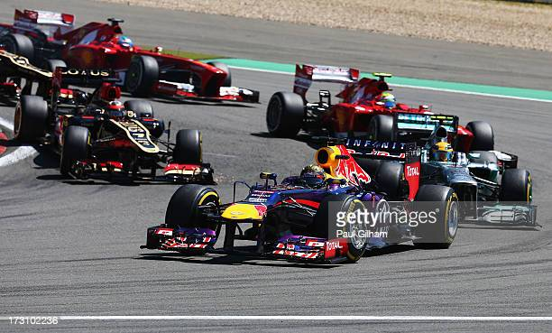 Sebastian Vettel of Germany and Infiniti Red Bull Racing leads the field into the first corner at the start of the German Grand Prix at the...