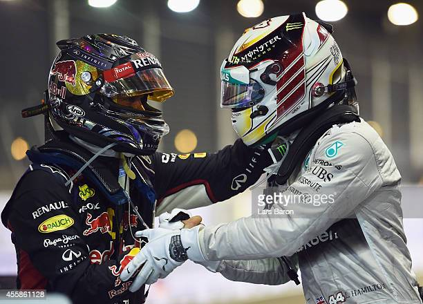 Sebastian Vettel of Germany and Infiniti Red Bull Racing congratulates Lewis Hamilton of Great Britain and Mercedes GP as they celebrate in Parc...