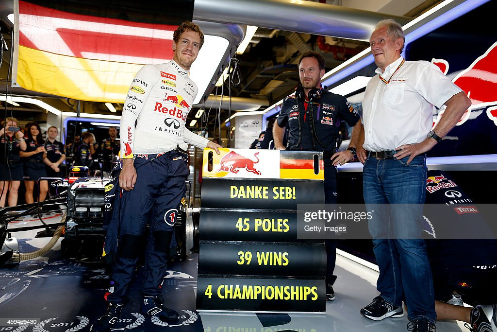 Sebastian Vettel of Germany and Infiniti Red Bull Racing poses with Infiniti Red Bull Racing Team Principal Christian Horner and team consultant Dr Helmut Marko next to a pit board displaying his achievements with the team in the garage before the Abu Dhabi Formula One Grand Prix at Yas Marina Circuit on November 23, 2014 in Abu Dhabi, United Arab Emirates.