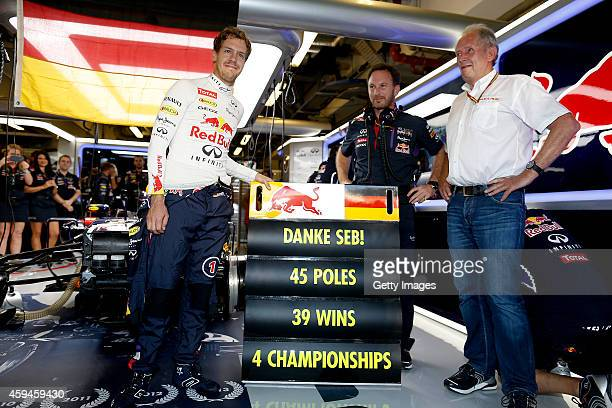Sebastian Vettel of Germany and Infiniti Red Bull Racing poses with Infiniti Red Bull Racing Team Principal Christian Horner and team consultant Dr...