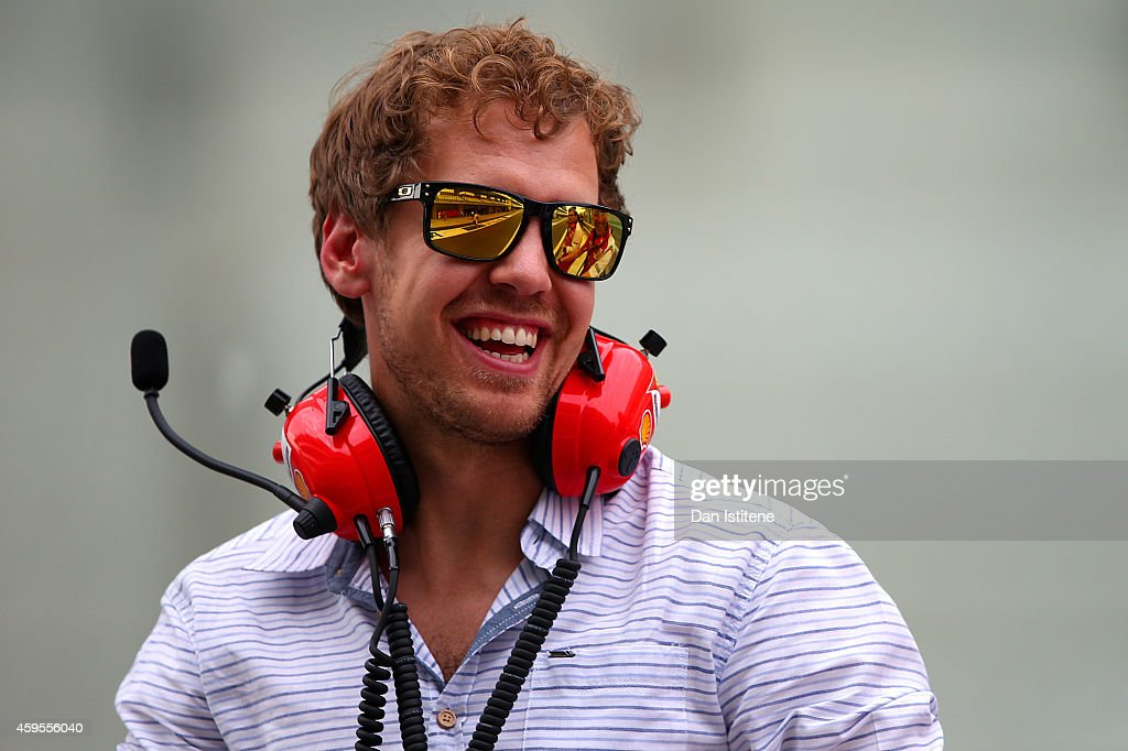 Sebastian Vettel of Germany and Infiniti Red Bull Racing smiles as he speaks with members of the Ferrari team on the pit wall during day one of Formula One testing at Yas Marina Circuit on November 25, 2014 in Abu Dhabi, United Arab Emirates.