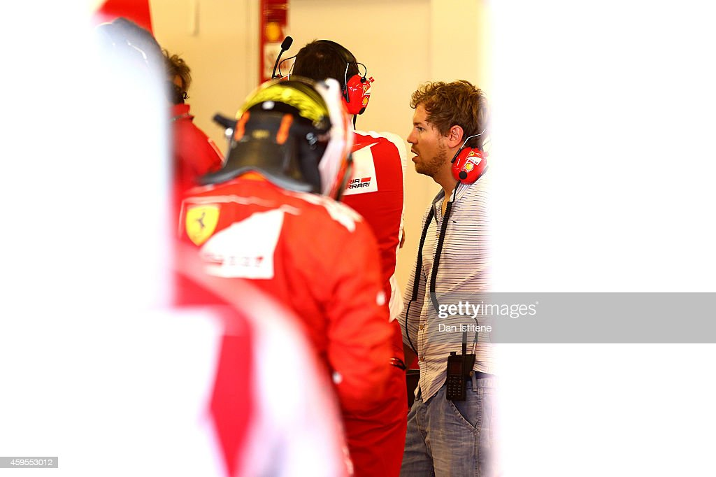 Sebastian Vettel of Germany and Infiniti Red Bull Racing speaks with his new team members in the Ferrari garage during day one of Formula One testing at Yas Marina Circuit on November 25, 2014 in Abu Dhabi, United Arab Emirates.