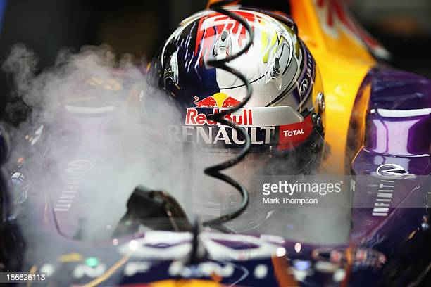 Sebastian Vettel of Germany and Infiniti Red Bull Racing uses dry ice to keep cool as he prepares to drive during qualifying for the Abu Dhabi...