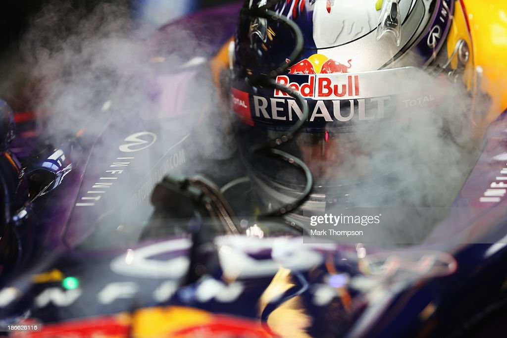 Sebastian Vettel of Germany and Infiniti Red Bull Racing uses dry ice to keep cool as he prepares to drive during qualifying for the Abu Dhabi Formula One Grand Prix at the Yas Marina Circuit on November 2, 2013 in Abu Dhabi, United Arab Emirates.