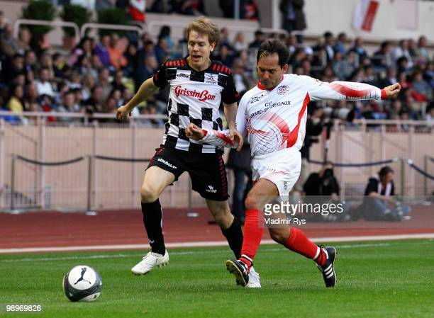Sebastian Vettel of Germany and Red Bull Racing and Alex Caffi battle for the ball during the football charity match between the Monaco star team and...