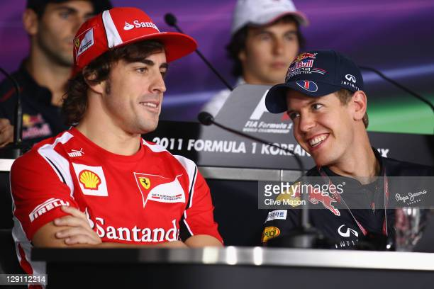 Sebastian Vettel of Germany and Red Bull Racing and Fernando Alonso of Spain and Ferrari attend the drivers press conference during previews to the...
