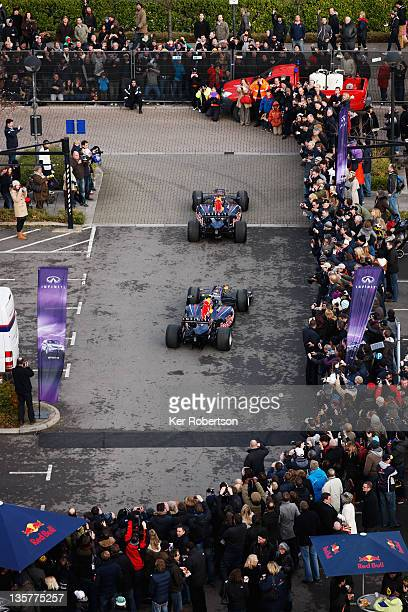Sebastian Vettel of Germany and Red Bull Racing and Mark Webber of Australia and Red Bull Racing drive thru the town streets while attending the Red...