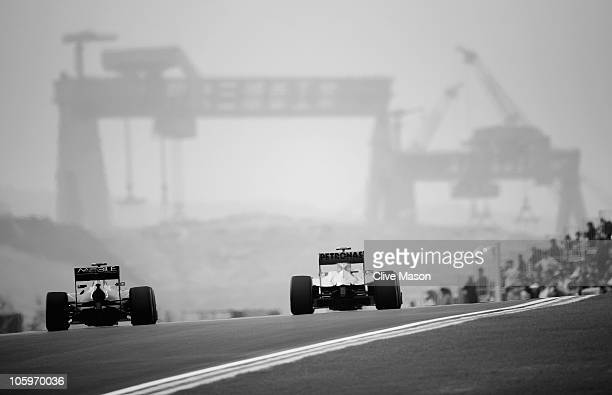 Sebastian Vettel of Germany and Red Bull Racing and Michael Schumacher of Germany and Mercedes GP drive side by side during the final practice...