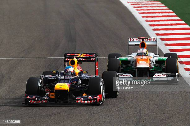 Sebastian Vettel of Germany and Red Bull Racing and Paul di Resta of Great Britain and Force India drive side by side during the Bahrain Formula One...