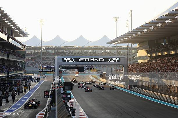 Sebastian Vettel of Germany and Red Bull Racing and Pedro de la Rosa of Spain and Hispania Racing Team queue up at the pitlane exit as Lewis Hamilton...