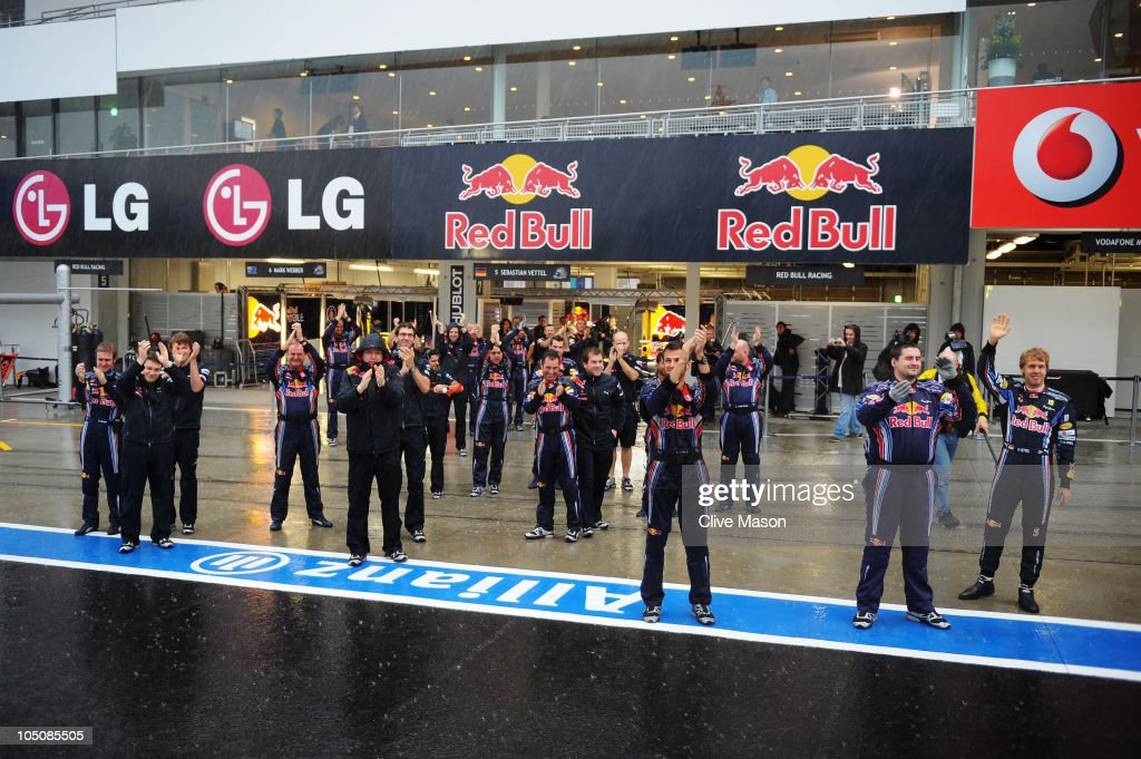 Sebastian Vettel (right) of Germany and Red Bull Racing and team mates wave to the crowd from outside their team garage as torrential rain causes the postponement of qualifying for the Japanese Formula One Grand Prix at Suzuka Circuit on October 9, 2010 in Suzuka, Japan.