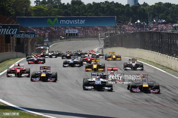 Sebastian Vettel of Germany and Red Bull Racing beats Nico Huelkenberg of Germany and Williams into turn one at the start of the Brazilian Formula...