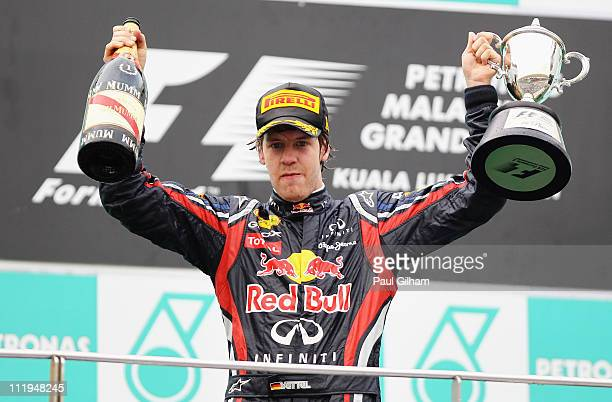 Sebastian Vettel of Germany and Red Bull Racing celebrates on the podium after winning the Malaysian Formula One Grand Prix at the Sepang Circuit on...
