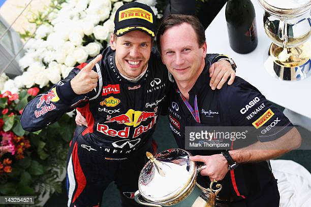 Sebastian Vettel of Germany and Red Bull Racing celebrates on the podium with his Team Principal Christian Horner after winning the Bahrain Formula...