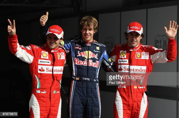 Sebastian Vettel of Germany and Red Bull Racing celebrates taking pole position with second placed Felipe Massa of Brazil and Ferrari and third...