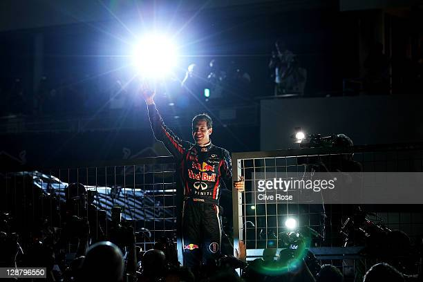 Sebastian Vettel of Germany and Red Bull Racing celebrates with team mates in the pitlane after finishing third to secure his second F1 World Drivers...
