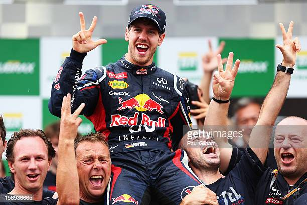 Sebastian Vettel of Germany and Red Bull Racing celebrates with team mates on the podium as he finishes in sixth position and clinches the drivers...