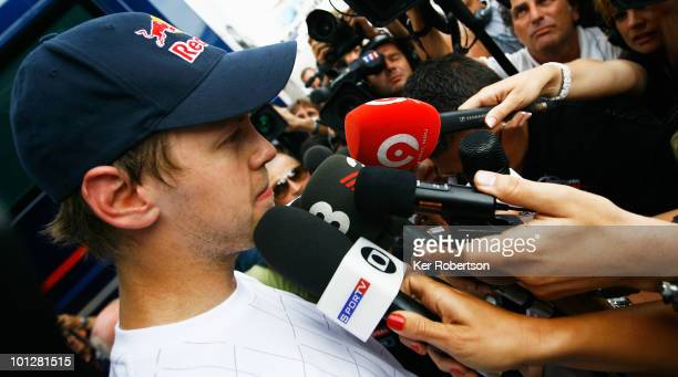 Sebastian Vettel of Germany and Red Bull Racing gives interview to the media in the paddock after colliding with his team mate Mark Webber of...