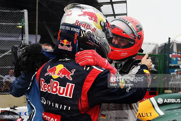 Sebastian Vettel of Germany and Red Bull Racing is congratulated by Michael Schumacher of Germany and Mercedes GP in parc ferme as he finishes in...