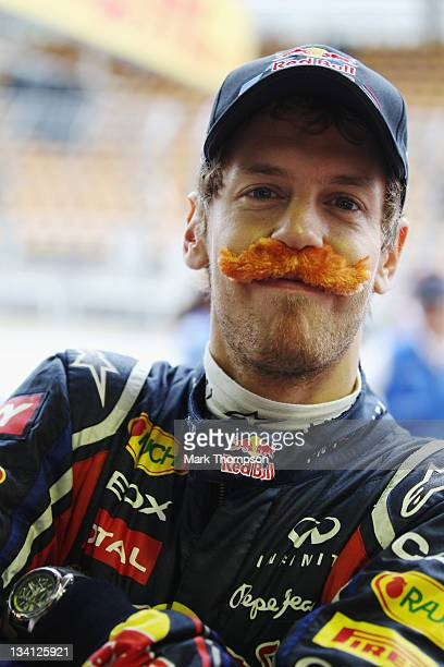 Sebastian Vettel of Germany and Red Bull Racing is seen wearing a false moustache as he celebrates breaking Nigel Mansells record after securing pole...