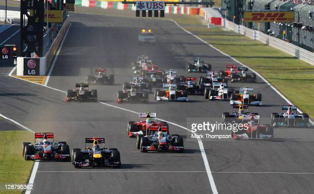 Sebastian Vettel of Germany and Red Bull Racing leads from Jenson Button of Great Britain and McLaren towards the first corner at the start of the...