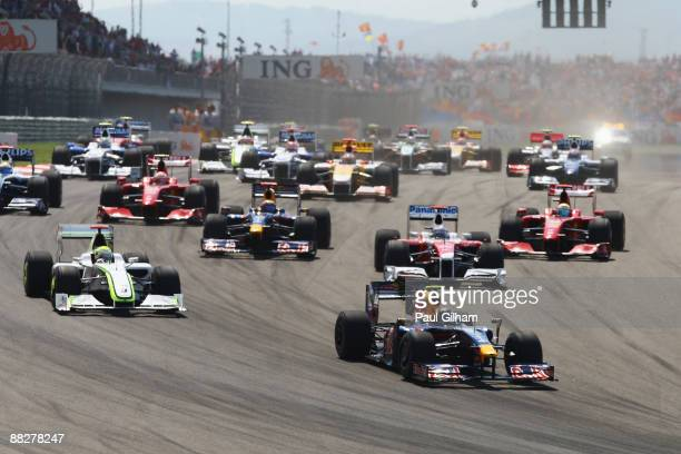 Sebastian Vettel of Germany and Red Bull Racing leads Jenson Button of Great Britain and Brawn GP into the first corner at the start of the Turkish...