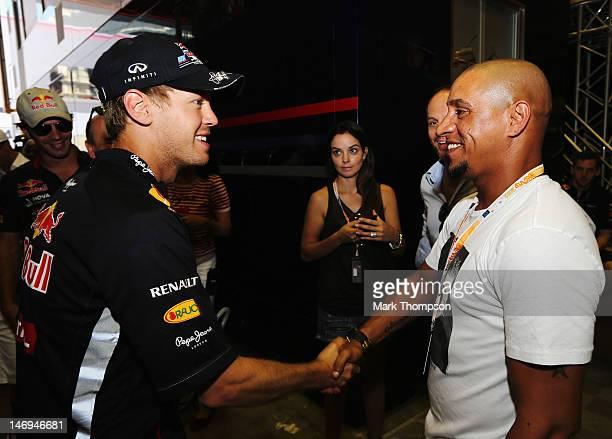 Sebastian Vettel of Germany and Red Bull Racing meets Brazilian footballer Roberto Carlos before the European Grand Prix at the Valencia Street...