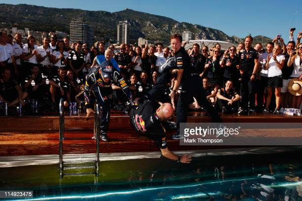 Sebastian Vettel of Germany and Red Bull Racing pushes Red Bull Racing Chief Technical Officer Adrian Newey and Team Principal Christian Horner into...