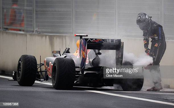 Sebastian Vettel of Germany and Red Bull Racing puts out a fire on his car during the Korean Formula One Grand Prix at the Korea International...