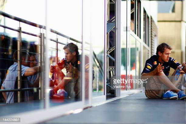 Sebastian Vettel of Germany and Red Bull Racing talks with Pirelli's motorsport director Paul Hembery and a Pirelli colleague following practice for...