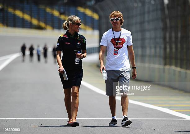 Sebastian Vettel of Germany and Red Bull Racing walks the track with his press officer Britta Roeske during previews to the Brazilian Formula One...