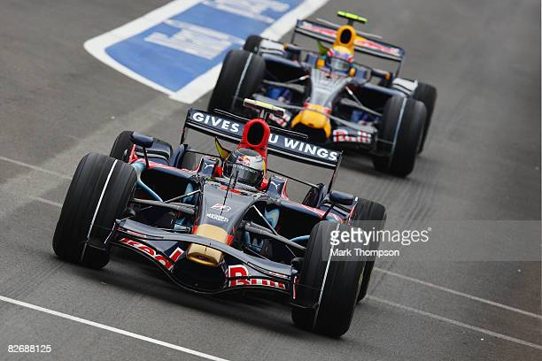 Sebastian Vettel of Germany and Scuderia Toro Rosso exits the pitlane in front of Mark Webber of Australia and Red Bull Racing during qualifying for...