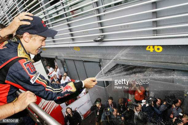 Sebastian Vettel of Germany and Scuderia Toro Rosso sprays champage as he celebrates with team mates in the paddock after winning the Italian Formula...