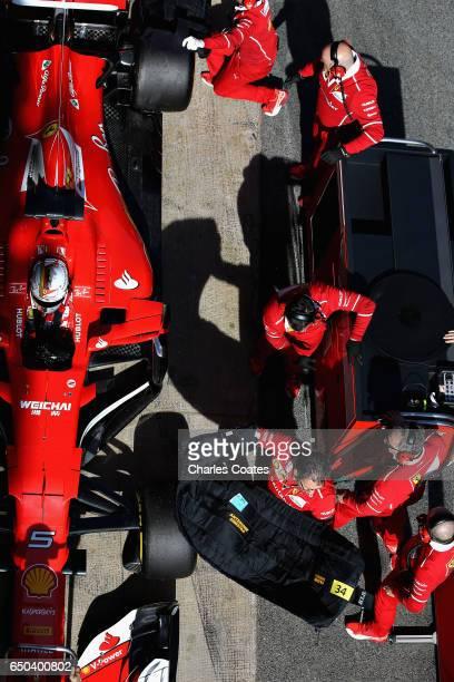 Sebastian Vettel of Germany driving the Scuderia Ferrari SF70H and the Ferrari team prepare for a race simulation in the Pitlane during day three of...